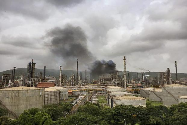 Smoke is seen after a fire broke out at a refinery of Bharat Petroleum after explosions in Chembur area of Mumbai on 8 August 2018. India on Friday banned the import of petcoke for use as fuel. Photo: PTI.